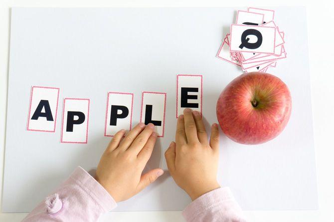 アルファベットのカードを並べて「APPLE」を作る子どもの手