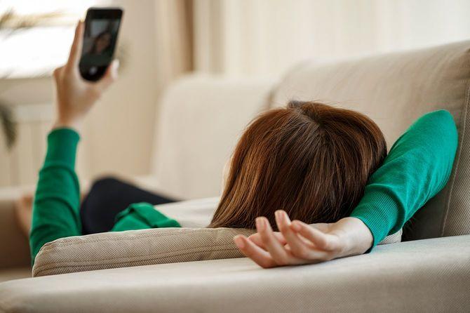 ソファーでスマホを眺める女性