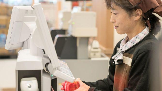 スーパーの店員がレジを使用している