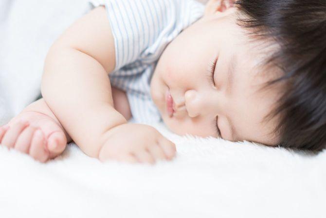 白い毛布の上に眠る赤ちゃん