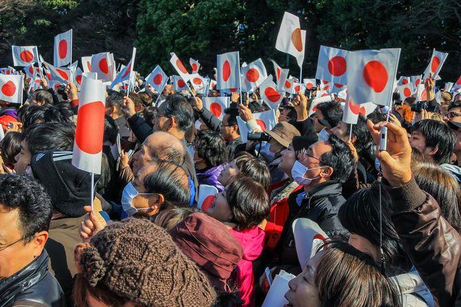 東京の正月初日に皇居前の広場にあるバルコニーの下の群衆