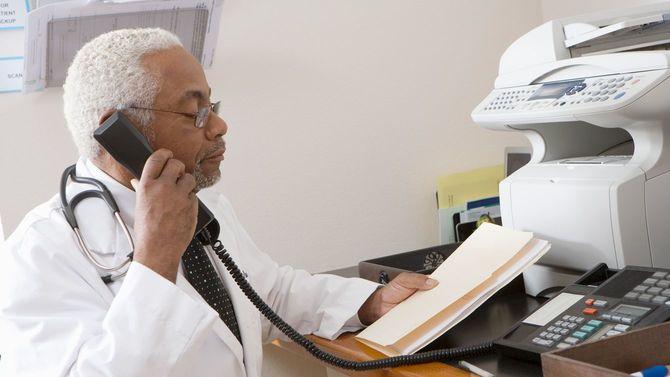 アフリカ系アメリカ人の老人男性医師が記録を確認しながら電話している