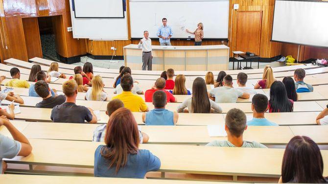 大学の大教室で講義をする教授やアシスタントたち