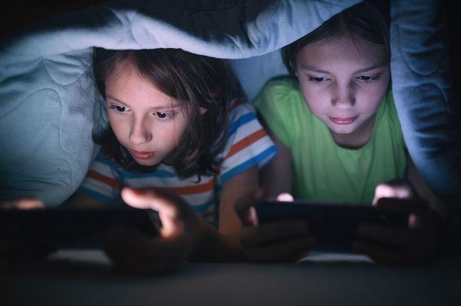 ベッドで携帯電話でゲームをしている少年と女の子