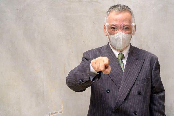 険しい表情でこちらを指さすマスクとフェイスシールドをつけたスーツの中年男性