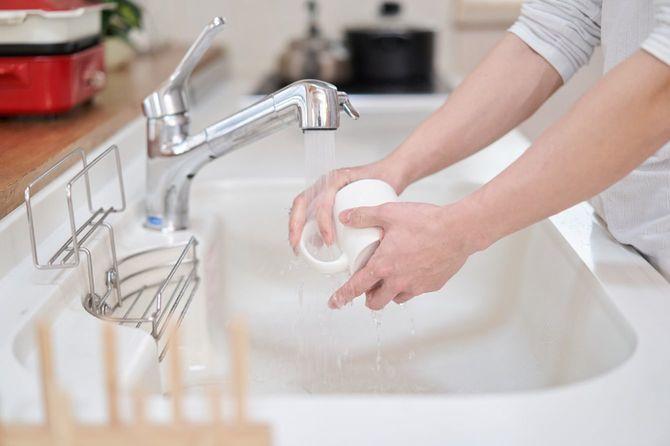 台所でカップを洗う男性の手元