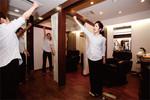 各店舗で毎朝5分ほど朝礼を行う。女性従業員たちは身振りを交えて大声でスローガンを唱和する。