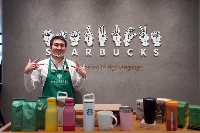 """nonowa国立店の店頭。ストアマネージャーの伊藤真也さんに手話で""""スターバックス""""を表してもらった"""