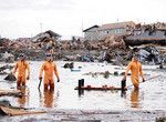 津波で一帯が破壊され、200人以上の遺体が見つかった仙台市若林区荒浜にて。右端の隊員のもつボートに遺体を乗せる。