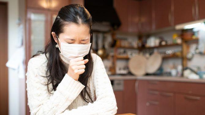 マスクを着用して咳をする女性