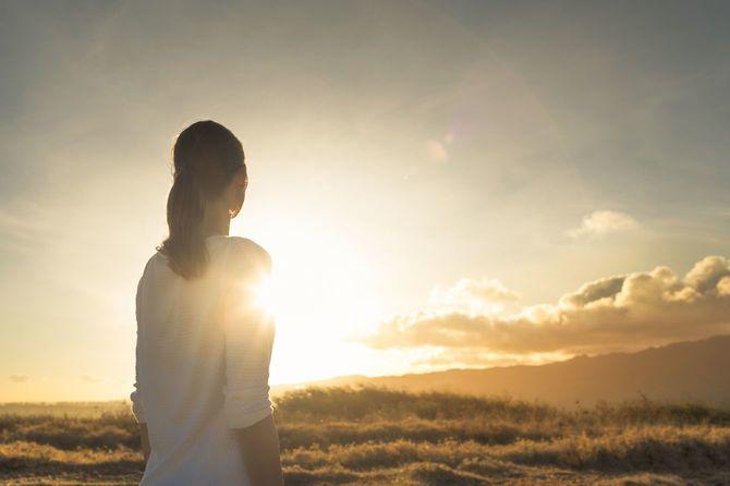 美しい黄昏を見つめながら山の上に立つ女性