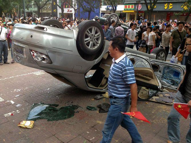 中国・西安で路上でひっくり返ったトヨタ車。反日官製デモ活動の参加者たちは、日本の尖閣諸島国有化に反対するデモの間、日本車を標的にした=2012年9月15日