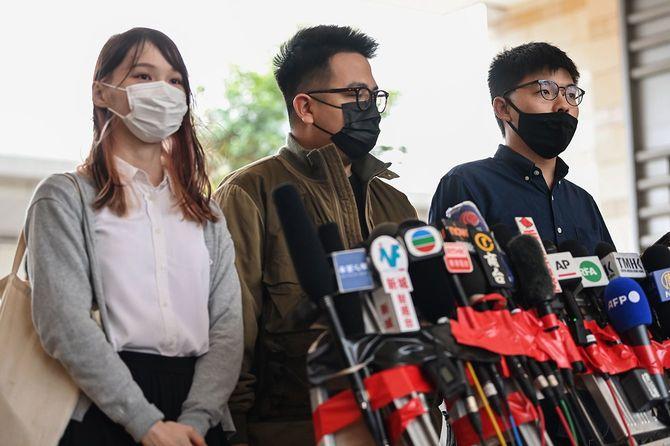 2019年の抗議活動に関連した無許可集会容疑で、2020年11月23日、裁判のために到着した後、メディアに向かって話す「香港衆志」の(左から)アグネス・チョウ、イワン・ラム、ジョシュア・ウォンの3人。
