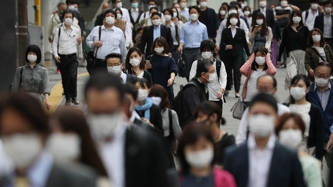 緊急事態宣言が解除されて初めての朝を迎え、多くの通勤客らが行き交う新宿駅付近=2020年5月26日、東京都新宿区