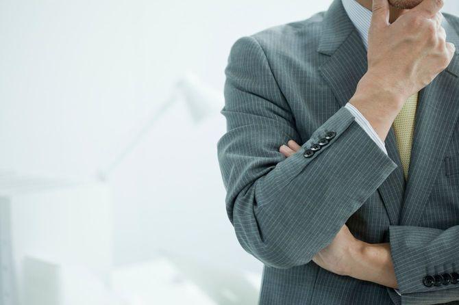 顎に手を当てて考えるビジネスマン