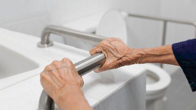 手すりに摑まる高齢女性