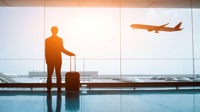 スーツケースを手に空港の窓から飛行機を眺める男性