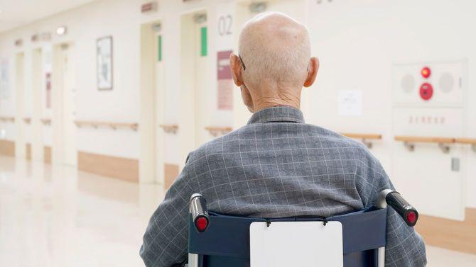 病院内を車椅子で移動する高齢男性