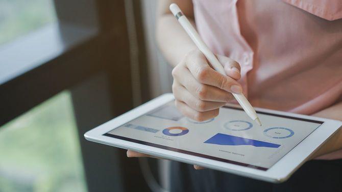 データ報告が表示されたタブレットを持つ女性マネジャーの手元