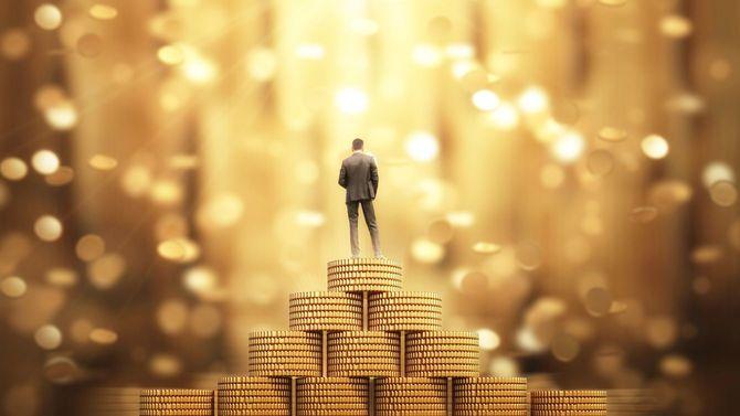 お金の雨の下で傘を立って実業家