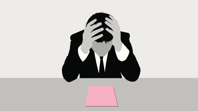 ピンクの書類を前に頭を抱える男性