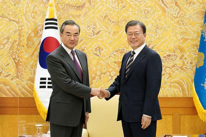 2020年11月26日、ソウルの大統領府での会談で、中国の王毅外相(左)と握手する韓国の文在寅大統領(右)