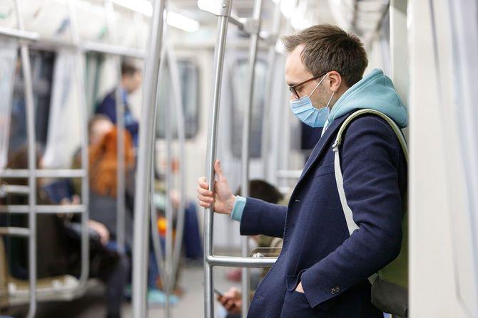 公共交通機関で保護マスクを着用している男性