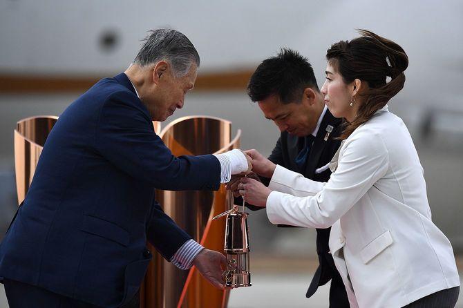 聖火が格納されたランタンをもつ柔道男子の野村忠宏さんとレスリング女子の吉田沙保里さん、2020年東京五輪・パラリンピック大会組織委員会の森喜朗会長