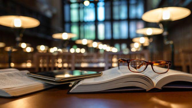 公共図書館の机の上に、開かれた本の上にタブレット端末とメガネがある
