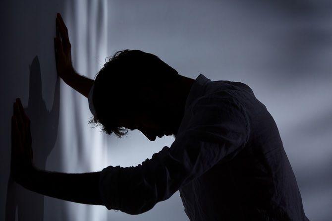 壁に手を当て苦しむ男性