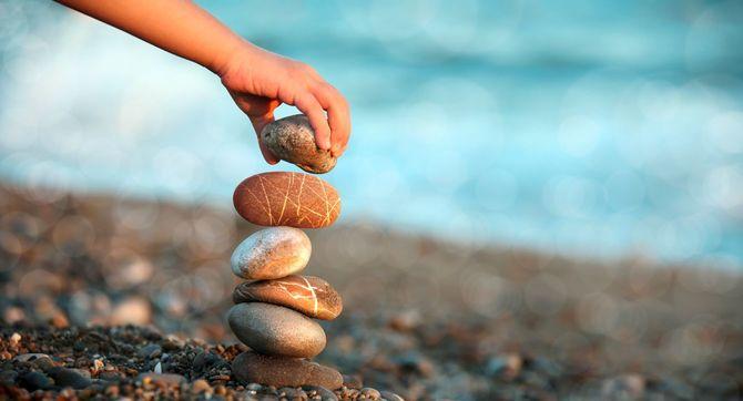 ビーチで石を積んで遊ぶ子供の手元