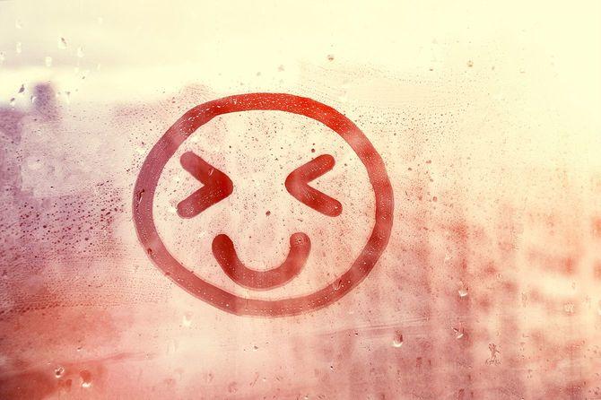 雨滴があふれた窓に描かれた幸せな笑顔