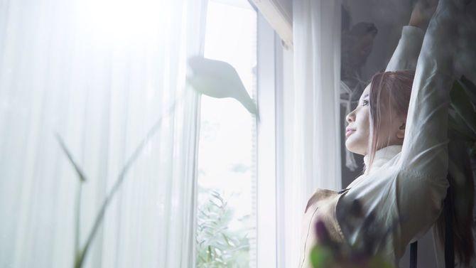 窓際の朝日に浴びながら伸びをする女性