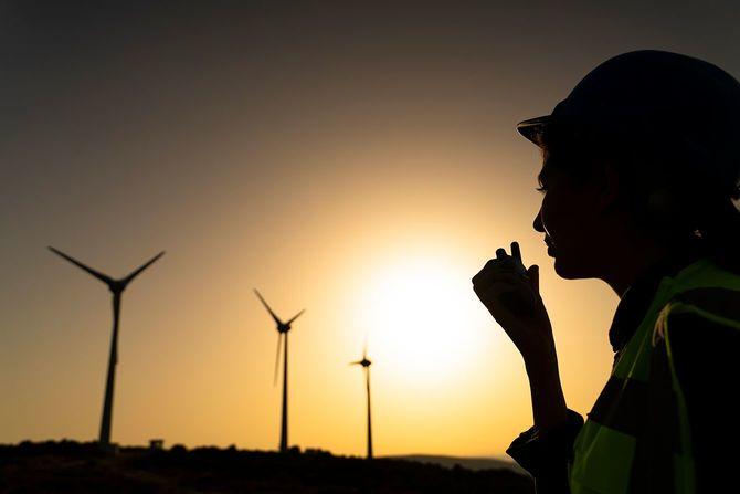 日没時に風力タービン農場で働く若いメンテナンスエンジニア